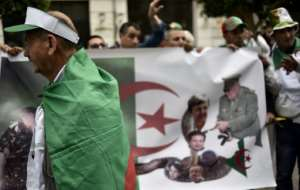 Algerian protesters parade a national flag showing the country still in the grip of key allies of Abdelaziz Bouteflika after the ailing president quit on Tuesday. By Ryad KRAMDI (AFP)