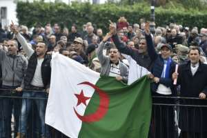 Algerian protesters shouted slogans supporting the upcoming elections near an anti-government demonstration in Algiers on December 9.  By RYAD KRAMDI (AFP/File)