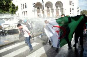 Algerian riot police spray anti-government protesters with water during a demonstration in the capital Algiers.  By RYAD KRAMDI (AFP)