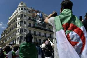 Algerian students watch a huge banner being unfurled on a building in the capital demanding the overthrow of the