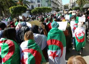 Algerian students, draped in national flags, protest Abdelkader Bensalah's appointment as interim president. By STRINGER (AFP)