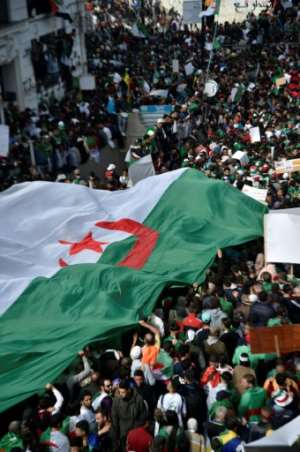 Algerians carry a giant national flag as they take part in an anti-government demonstration in Algiers. By RYAD KRAMDI (AFP)