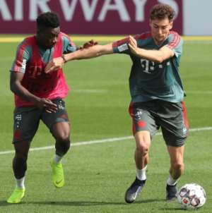 Alphonso Davies (L) spars with Germany midfielder Leon Goretzka (R) during a training session with Bayern Munich in Doha..  By KARIM JAAFAR (AFP)