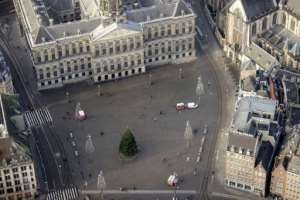 Amsterdam's Dam square is deserted but for a solitary Christmas tree as the country goes through a five-week lockdown.  By ROBIN VAN LONKHUIJSEN (ANP/AFP)