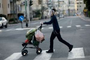 An ultra-Orthodox Jewish youth wearing a protective plastic mask crosses a street with his shopping in the Israeli city of Bnei Brak near Tel Aviv.  By MENAHEM KAHANA (AFP)