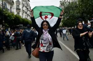 An Algerian woman waves a national flag as she takes part in an anti-government demonstration in the capital Algiers on March 14.  By RYAD KRAMDI (AFP/File)