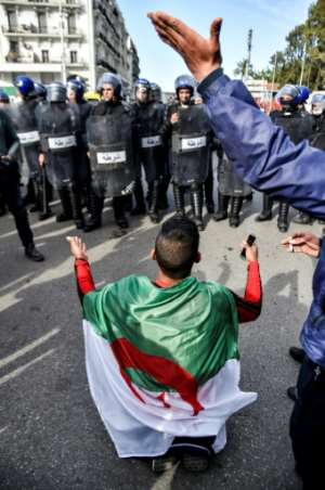 An Algerian youth draped in a national flag chants slogans while kneeling before riot police. By RYAD KRAMDI (AFP)