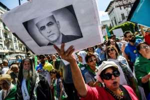 An Algerian protester holds up a rights campaigner Kamel Eddine Fekhar who died in custody on Tuesday.  By RYAD KRAMDI (AFP)