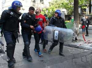 An Algerian riot policeman escorts a comrade amidst clashes with protesters in Algiers. By - (AFP)