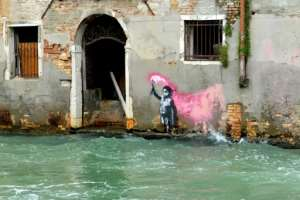 An alleged work by British street artist Banksy depicting a migrant child wearing a lifejacket holding a pink flare is painted on the outer wall of a house in Venice.  By Marco SABADIN (AFP/File)