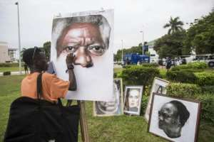 An artist paints a portrait of Kofi Annan outside the Accra International Conference Centre where the coffin of the Ghanaian diplomat and former UN Secretary General lay in state.  By CRISTINA ALDEHUELA (AFP)