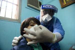 An Egyptian doctor adjusts the protective mask covering a young patient's face at the infectious diseases unit of a Cairo hospital.  By Ahmed HASAN (AFP/File)