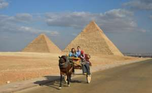 An Egyptian drives a horse-drawn cart with a couple of tourists at the Giza pyramids on the southwestern outskirts of the Egyptian capital Cairo on December 29, 2018.  By MOHAMED EL-SHAHED (AFP)