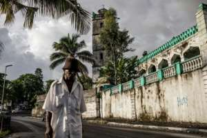 An elderly resident walks past a mosque in downtown Moroni. The grind of poverty in the Comoros can be worsened by comparisons with Mayotte, the island that chose to remain under French rule. By GIANLUIGI GUERCIA (AFP)