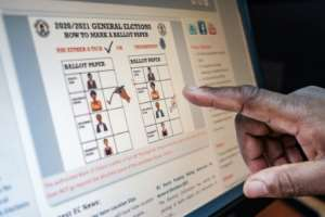 An electoral commission staff member gestures towards a screen displaying how a ballot paper should be marked during the upcoming election.  By SUMY SADURNI (AFP)