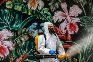 An employee wearing protective gear disinfects a shopping mall as a preventive measure against COVID-19 in Caxias do Sul, Brazil.  By SILVIO AVILA (AFP)