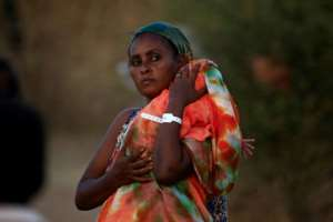 An Ethiopian mother carries her baby in the Um Raquba refugee camp in eastern Sudan, where she fled to from fighting in her homeland of Tigray; healthcare facilities are severely limited.  By ASHRAF SHAZLY (AFP)