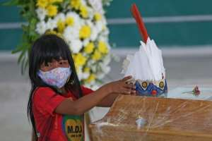 An indigenous girl from Parque das Tribos community leaves a headdress on the coffin of Chief Messias, 53, of the Kokama tribe who died of COVID-19, in Manaus, Brazil.  By MICHAEL DANTAS (AFP)
