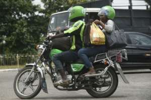 An ORide driver, decked out in bib and helmet, takes a passenger through the Lagos gridlock.  By PIUS UTOMI EKPEI (AFP)