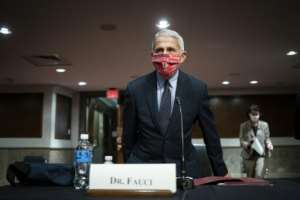 Anthony Fauci, the top US infectious disease expert, has warned that the country is still 'knee-deep' in its first coronavirus wave.  By POOL (GETTY IMAGES NORTH AMERICA/AFP)