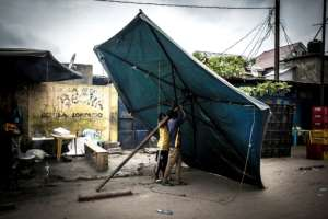 As the waiting game continues, a parasol comes in handy in Kinshasa's Victoria district.  By John WESSELS (AFP)