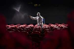 Astaff member sprays disinfectant at a cinema as it prepares to reopen to the public in Shenyang, China.  By STR (AFP)