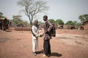 Awatche's self-defence leader shakes hands with a Fulani breeder in the village. By FLORENT VERGNES (AFP)