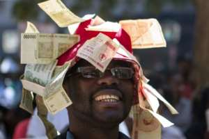 Attempts by African countries to get around fiscal constraints didn't always end well, such as this Zimbabwean man who decorated his hat with worthless currency.  By ZINYANGE AUNTONY (AFP/File)