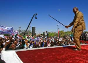 Bashir performs with his cane as he addresses a rally of his supporters in the capital Khartoum in January last year.  By ASHRAF SHAZLY (AFP)