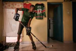 Benjamin Mburu, a Kenyan hockey player, practices stick work in his living room in Nairobi, Kenya, on May 19, 2020, with all training suspended by lockdowns.  By Yasuyoshi CHIBA (AFP)