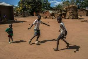 Boys play with a football made out plastic waste in the village where Lazarus Chakwera grew up.  By AMOS GUMULIRA (AFP)