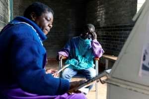 Blessing Chingwaru, an HIV positive and TB patient, has a consultation with a nurse at the Rutsanana clinic.  By Jekesai NJIKIZANA (AFP)