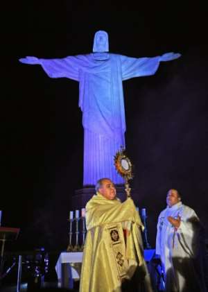 Brazilian Archbishop Cardinal Dom Orani celebrates Easter Mass at the Christ Redeemer statue in Rio de Janeiro, where the landmark had a doctor's uniform projected onto it in honour of all the medical staff worldwide fighting the coronavirus pandemic.  By CARL DE SOUZA (AFP)