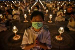 Buddhist worshippers wearing protective masks attend prayers at Wat Dhammakaya Buddhist temple in Bangkok -- Thailand has announced 14 confirmed coronavirus infections.  By Lillian SUWANRUMPHA (AFP)