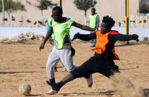 Cameroonian (orange) and Senegalese (yellow) migrants play football at the Libyan Interior Ministry's illegal immigration shelter in Tajoura, Tripoli, on February 28, 2018.  By MAHMUD TURKIA (AFP)