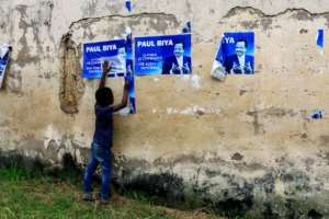 Cameroonian President Paul Biya, seen here in posters, vowed address needs of anglophone areas, but the conflict continues.  By STR (AFP)