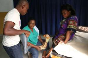 Car accident victim Adjovi Koudahe, 46, says she has 'high hopes' for her 3D-printed orthotic leg brace, here being fitted at Togo's national orthopaedic and physiotherapy centre.  By MATTEO FRASCHINI KOFFI (AFP)