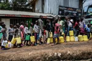 Children wait in line for water, distributed for free in the Nairobi slum of Kibera last week. Health experts say close queueing breaks the rule of social distancing to prevent virus infection.  By Gordwin ODHIAMBO (AFP)