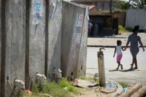 Communal toilets in the informal settlement often overflow, spilling human waste onto the street.  By RODGER BOSCH (AFP)