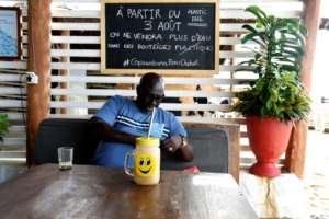 Cool and green: A customer sips his drink through a metal straw. The Copacabana describes itself as the first in Senegal to make the switch to 'zero plastic'.  By SEYLLOU (AFP)
