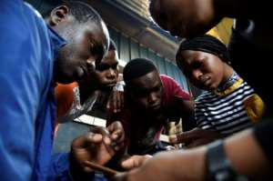 Code for Africa's John Eromosele, left, teaches volunteers how to use the app for the digital mapping project.  By PIUS UTOMI EKPEI (AFP)