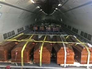Coffins containing the remains of 20 Egyptian Coptic Christians beheaded by jihadists on the beach in Sirte in 2015 are loaded onto a plane in Misrata on May 14, 2018, before being sent to Cairo.  By MAHMUD TURKIA (AFP)