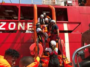 Crew on the Ocean Viking rescue ship, operated by French NGOs SOS Mediterranee and Medecins sans Frontieres (MSF), help a young child aboard.  By Anne CHAON (AFP)