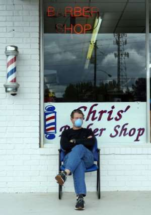 Dan Settle sits outside Chris' Barber Shop as he waits his turn for a haircut in Lilburn, Georgia on April 24, 2020.  By Tami Chappell (AFP)