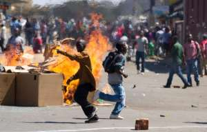 Demonstrators in Harare began throwing stones at police while some set tyres ablaze and others pulled down the sign for a street named after Mugabe