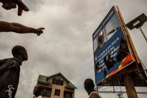 Demonstrators point at a broken billboard showing the face of Democratic Republic of Congo President Joseph Desiree Kabila during an opposition rally in Kinshasa