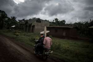 Deadly: Three Congolese on a motorbike in the Ebola-hit DRC province of North Kivu head to a graveyard, carrying a cross.  By John WESSELS (AFP)