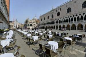 Deserted tables in front of the Doge palace in Venice, Italy.  By ANDREA PATTARO (AFP)