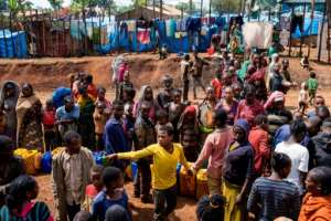 Displaced Gedeo people wait in line for a water at a camp, after fleeing their homes.  By Maheder HAILESELASSIE TADESE (AFP)