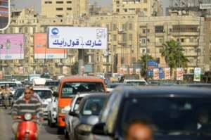 Egyptians drive under a banner reading in Arabic